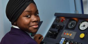 Abida gets to grips with driving a train using Network Rail's driver simulator at Basingstoke
